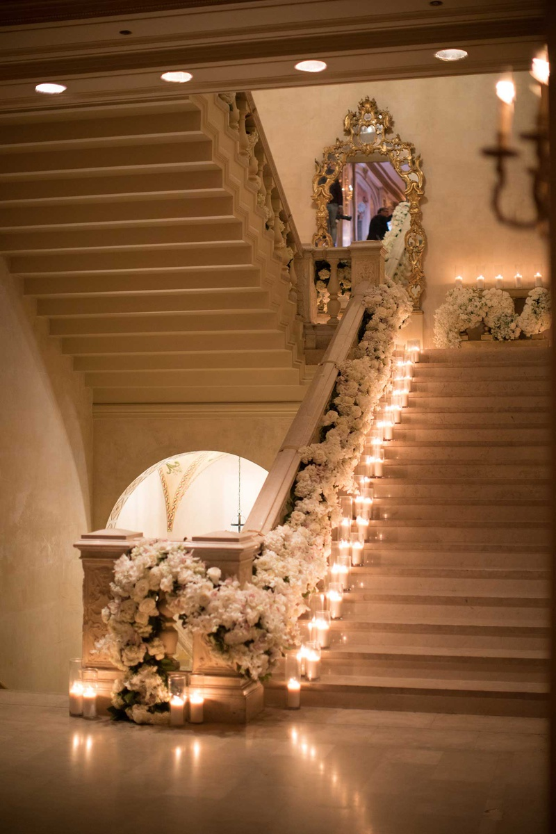 wedding at the plaza hotel candles on staircase mirror white flower runner down railing