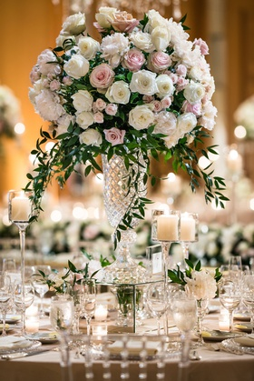 tall wedding reception centerpiece white pink rose peony flowers with greenery crystal vase candles