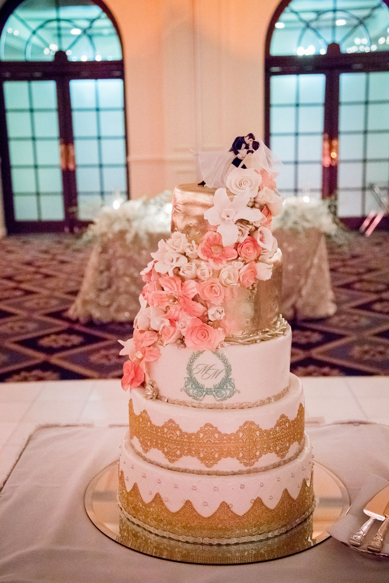 Wedding cake with gold details and sugar flowers in white and pink classic cake topper monogram