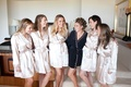 Bride with bridesmaids wearing robes in bridal suite