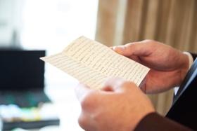 Groom reading note from bride on wedding day in groom's suite notecard