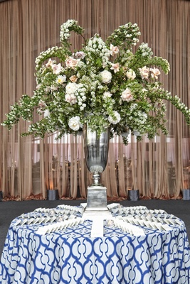 Place card table with blue and white linen, and large flower centerpiece