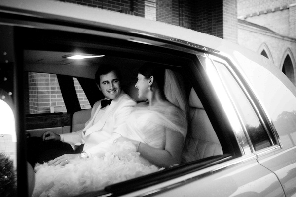 Black and white photo of newlyweds in limo