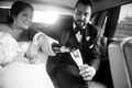 Black and white photo of bride and groom pouring champagne into flutes in back of Rolls Royce