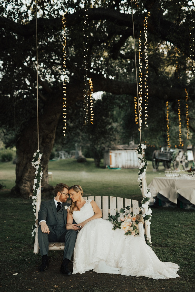 bride and groom leaning against each other on swinging hanging wrapped in vines hanging from tree