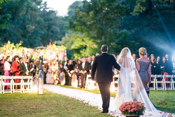 Guests at outdoor jewish wedding ceremony waiting for bride looking at her grand entrance down aisle