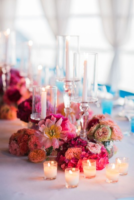 tea lights in front of floral centerpiece with bright pink and peach flowers
