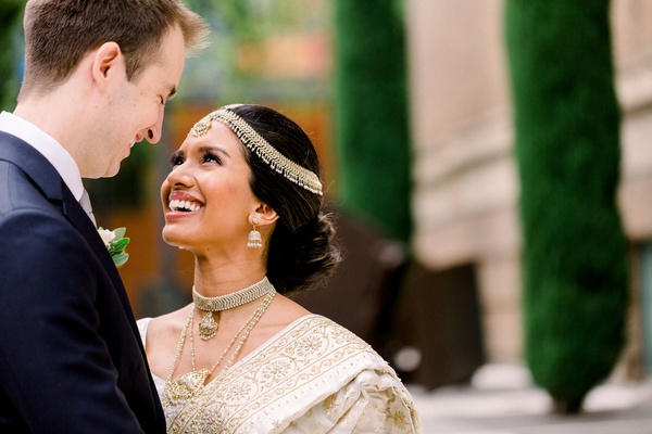 south asian bride in gold sari gazing up at white groom in suit