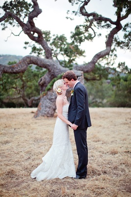Bride and groom holding hands in front of tree