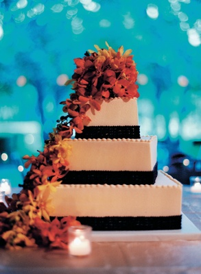 Wedding cake with brown bands and orange and yellow flowers