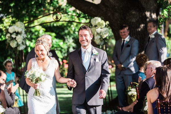 Bride in a sleeveless Claire Pettibone dress walks with groom in grey suit after a garden ceremony