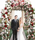 newlyweds underneath colorful floral arch pelican hill resort wedding newport beach california berta