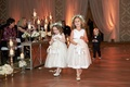 Flower girls walking down aisle with ring bearer behind baby's breath flower crowns white dresses
