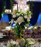 gold candelabrum wrapped with greenery and white flowerson crystal stand
