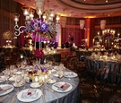 Silver table linens with clear oval back chairs at wedding reception