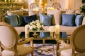 wedding reception lounge gold mirror coffee table white flowers candles light blue and navy pillows