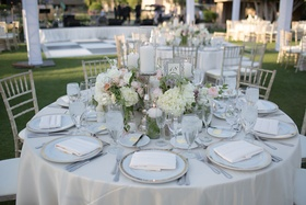 Outdoor wedding reception table with white roses, hydrangeas, peach and pink peonies, purple roses