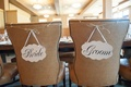 Bride and groom in calligraphy on die cut wedding signs on back of chairs