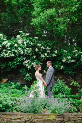 bride in romona keveza legends and groom in brooks brothers hand hands in the garden
