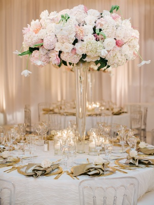 Wedding reception table with centerpiece of white and pink flowers, golden flatware, napkins