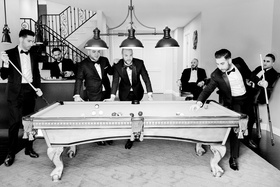 black and white photo of groom and groomsmen playing pool before wedding