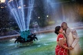 Indian couple kissing by a New Orleans fountain