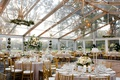 wedding reception clear tent with gold chandelier greenery white flower centerpieces