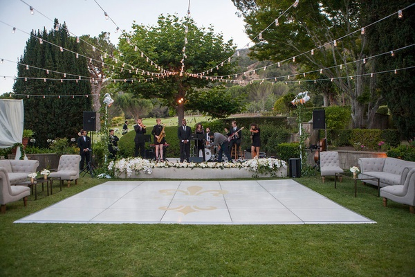 white outdoor dance floor couples gold logo strings of lights lounge furniture stage live band
