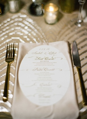 First course, pasta course, entree, dessert on oval menu atop champagne silk napkin and sequin linen