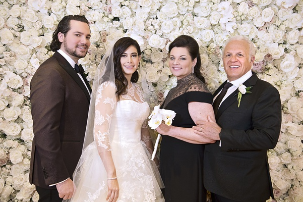 family wedding portrait in front of flower wall, bride in vera wang