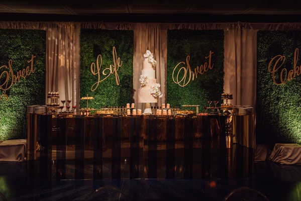 wedding cake and desserts on table in front of hedge wall with gold calligraphy signs sweet life