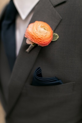 Groomsman in grey suit, navy pocket square, light orange ranunculus boutonniere