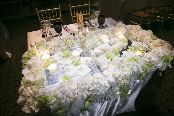 Wedding sweetheart table with square containers, floating candles, white & green orchids