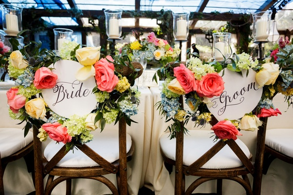 Wedding reception wood chair bride and groom calligraphy sign with bright colorful flower decor