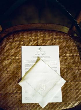 Ceremony program and handkerchief on guest seat at wedding ceremony with custom monogram