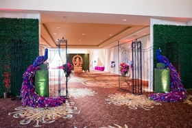 indian wedding gate framed by peacocks made from flowers and greenery wall