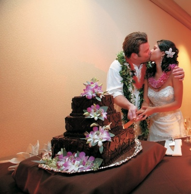 newlyweds cut chocolate cake with pink flowers
