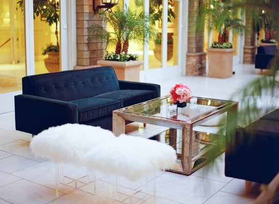 Mirror coffee table with navy blue sofa and fur stools