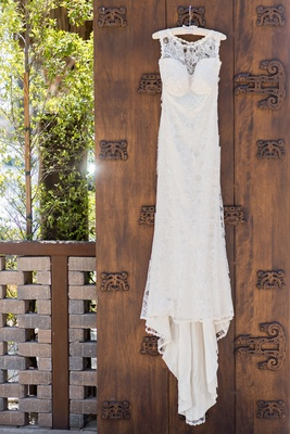 Claire Pettibone wedding dress on white hanger before wedding ceremony wood door at venue