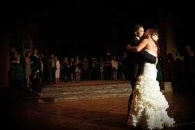 Bride and groom kiss on wood dance floor at reception