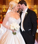 Bride in strapless Pnina Tornai wedding dress from Kleinfeld bridal with white bouquet and groom