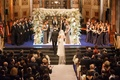 Groom leads bride to four-post chuppah made of branches and decorated with white orchids