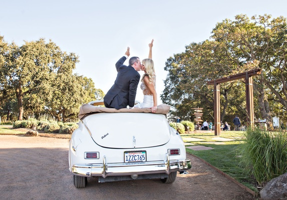 2bfe8227e56 ... Bride and groom in vintage convertible packard car white with peace  signs on back of seat  Wedding ...