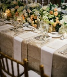 Wedding reception tablescape low flower runner with beige damask linen gold candle votives napkins