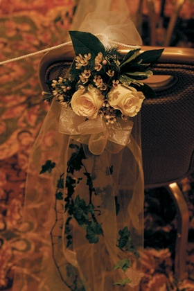Flower and greenery on backs of wedding chairs