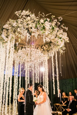 Bride and groom exchanging vows wedding ceremony flower chandelier strands or orchids and crystals