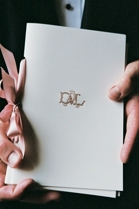 White ceremony booklets tied with pink ribbon