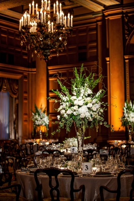 tall centerpiece with white flowers and green branches