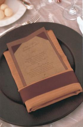 orange napkin holds brown menu card