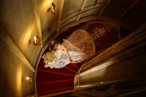 bride in lace monique lhuillier wedding dress red carpet spiral staircase portrait
